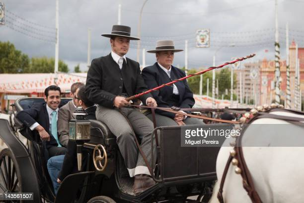 A traditional horsedrawn carriage rides through the Seville April Fair on April 28 2012 in Seville Spain Dating back to 1847 the fair usually begins...