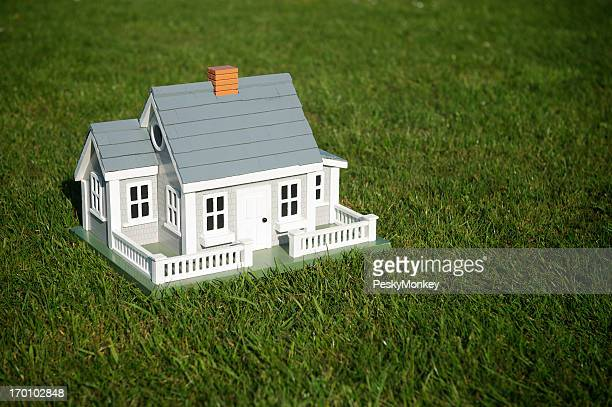 Traditional House Model Home Stands in Thick Green Grass