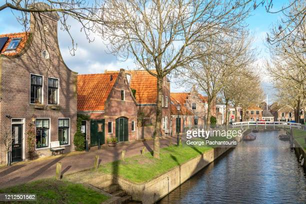 traditional houses and canal in medemblik, the netherlands - village stock pictures, royalty-free photos & images