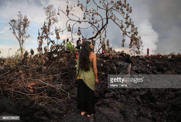 A traditional hula practitioner holds an offering on a recent lava flow from a Kilauea volcano fissure on Hawaii's Big Island on May 27 2018 in Pahoa...