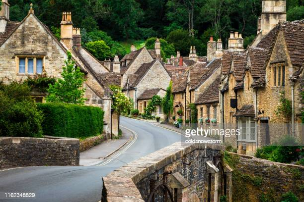 traditional idyllic english countryside village with cosy cottages and narrow road - village stock pictures, royalty-free photos & images