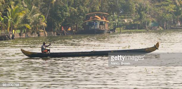 Traditional Indian Man in Indian Snake Boat in Kerala Backwaters in S. India.