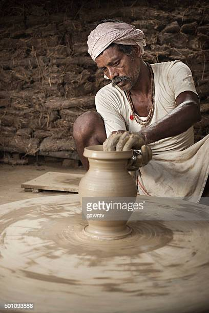 Traditional Indian potter making clay pot on manual pottery wheel.