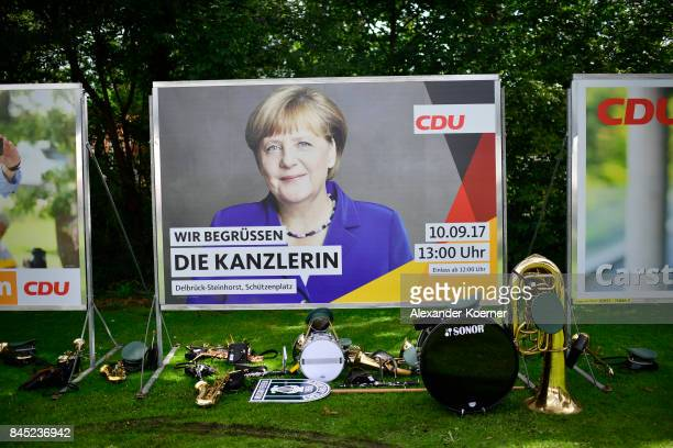 Traditional instruments stand in front of a billboard of German Chancellor and Christian Democrat Angela Merkel prior her speech to supporters at a...
