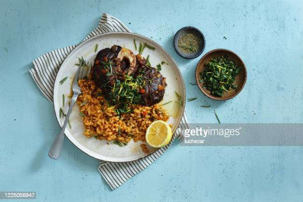 traditional italian osso buco with creamy saffron risotto and gremolata - beef stock pictures, royalty-free photos & images