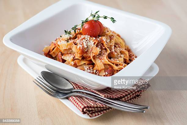 Traditional italian pasta tagliatelle with bolognese sauce or ragu with cherry tomato, thyme and parmesan cheese in a plate