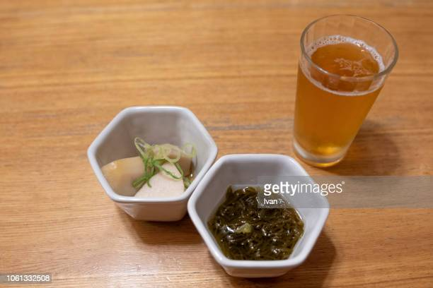 traditional japanese food,  tsukemono, pickled things, pickled vegetables with a cup of beer on wooden table overhead view - pickled ginger stock pictures, royalty-free photos & images