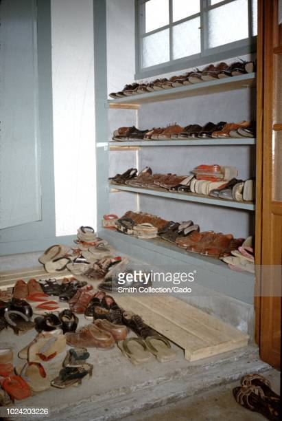 Traditional Japanese Genkan, or entryway used for the ceremonial removal of shoes prior to entering a dwelling, stacked with many pairs of shoes,...