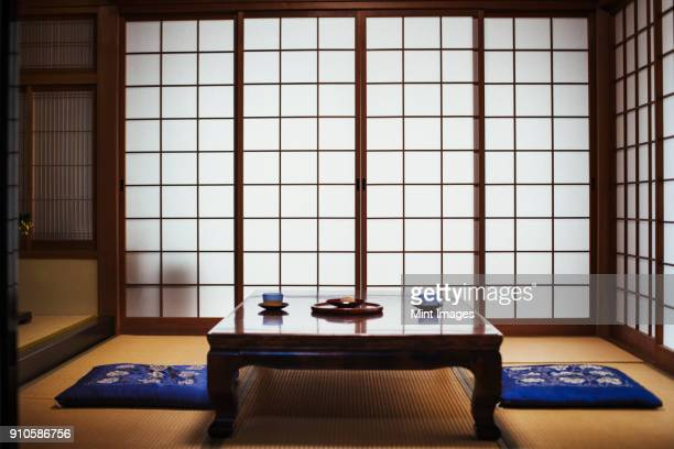 traditional japanese interior with low table set with bowls of tea. - tempel stock-fotos und bilder