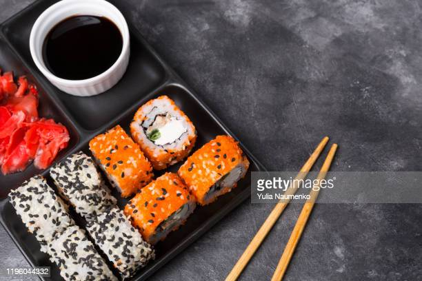 traditional japanese sushi menu. closeup of japanese plate with sushi rolls and ginger and soy sauce. there are sushi rolls with salmon, sashimi. - maki sushi stock pictures, royalty-free photos & images