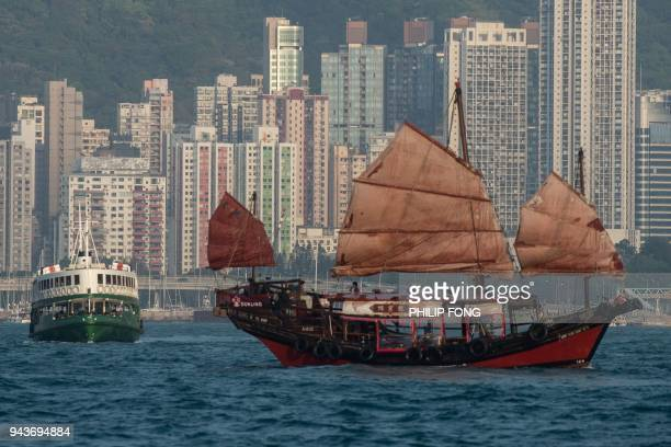 A traditional junk boat sails past a star ferry in Hong Kong's Victoria Harbour on April 9 2018 / AFP PHOTO / Philip FONG