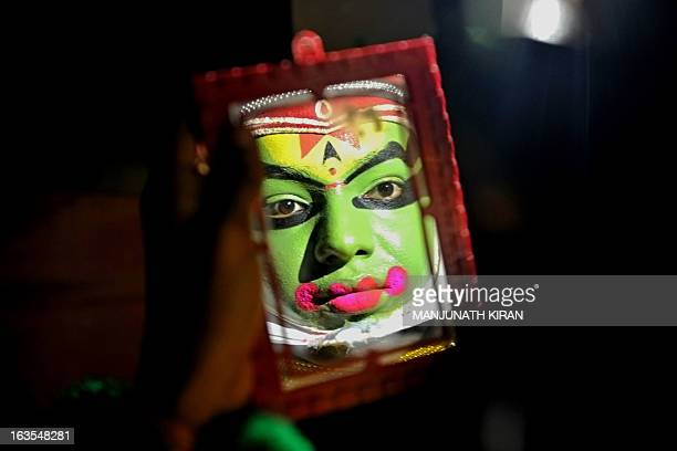 A traditional Kathakali performer puts on makeup before an event organised by India's Kerala state Tourism Department in Bangalore on March 12 2013...