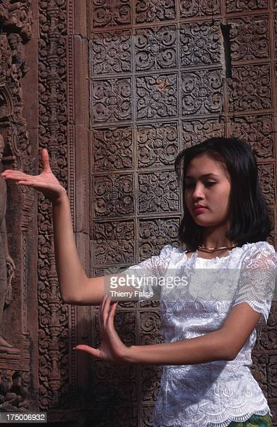 Traditional Khmer dancer, with the wooden carved decor of Banteay Srei temple in the background. Classical Khmer dance was introduced in the seventh...