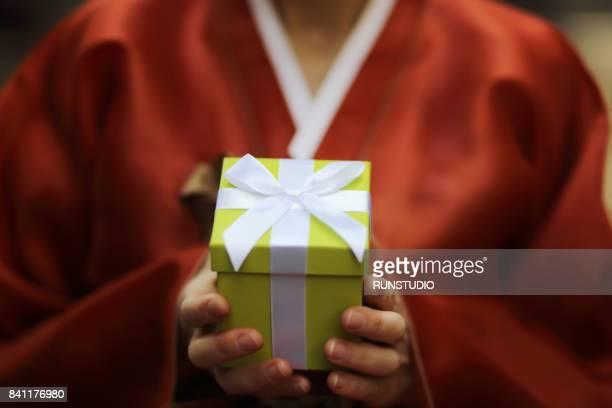 traditional Korean woman with a gift box