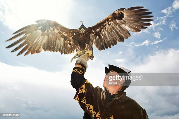 traditional kyrgyz hunter holding eagle - kazakhstan stock pictures, royalty-free photos & images