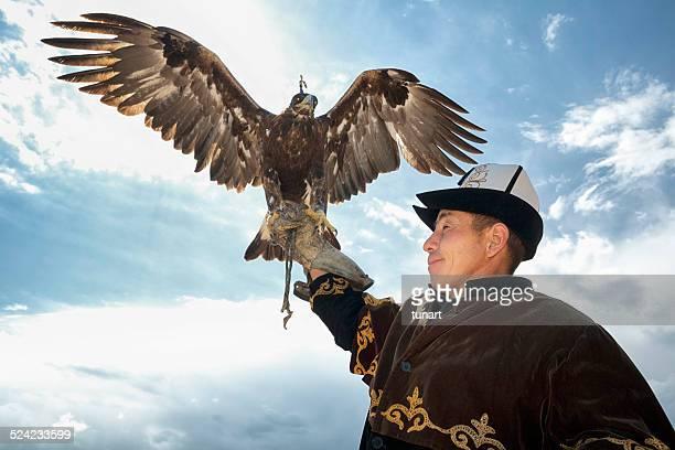 traditional kyrgyz hunter holding eagle - kirgizië stockfoto's en -beelden