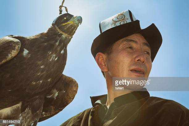 traditional kyrgyz hunter holding eagle - kyrgyzstan stock pictures, royalty-free photos & images