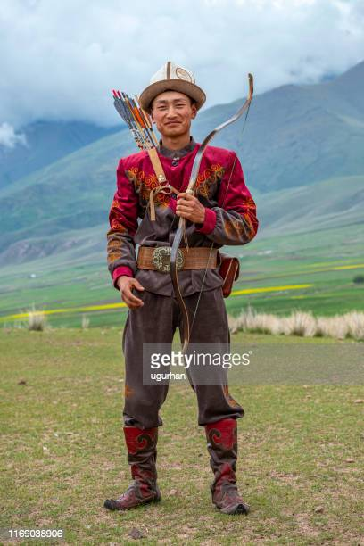 traditional kyrgyz hunter holding traditional arrow. - pic hunter stock pictures, royalty-free photos & images