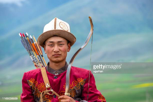 traditional kyrgyz hunter holding traditional arrow. - kazakhstan stock pictures, royalty-free photos & images