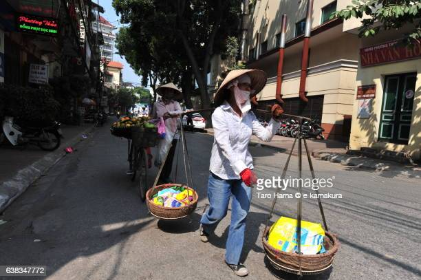 Traditional ladies carrying daily necessities or fruits by balance and bicycle