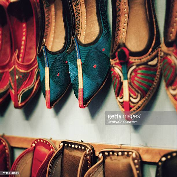 Traditional leather embroidered shoes known as khussas hang for sale in a shop in the Indian city of Jodhpur on April 14 2016 Rajasthan's 'Blue City'...