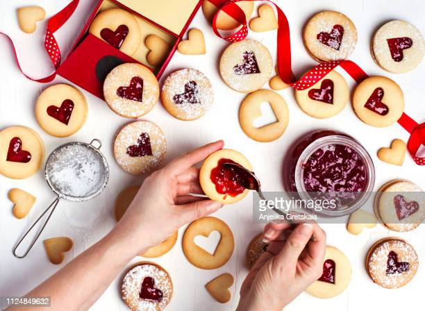 traditional linzer cookie with strawberry jam, top view. female hands making cookies. - valentine's day holiday stock pictures, royalty-free photos & images