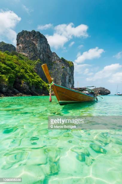 traditional longtail boat moored in phi phi islands, thailand - asiatisches langboot stock-fotos und bilder