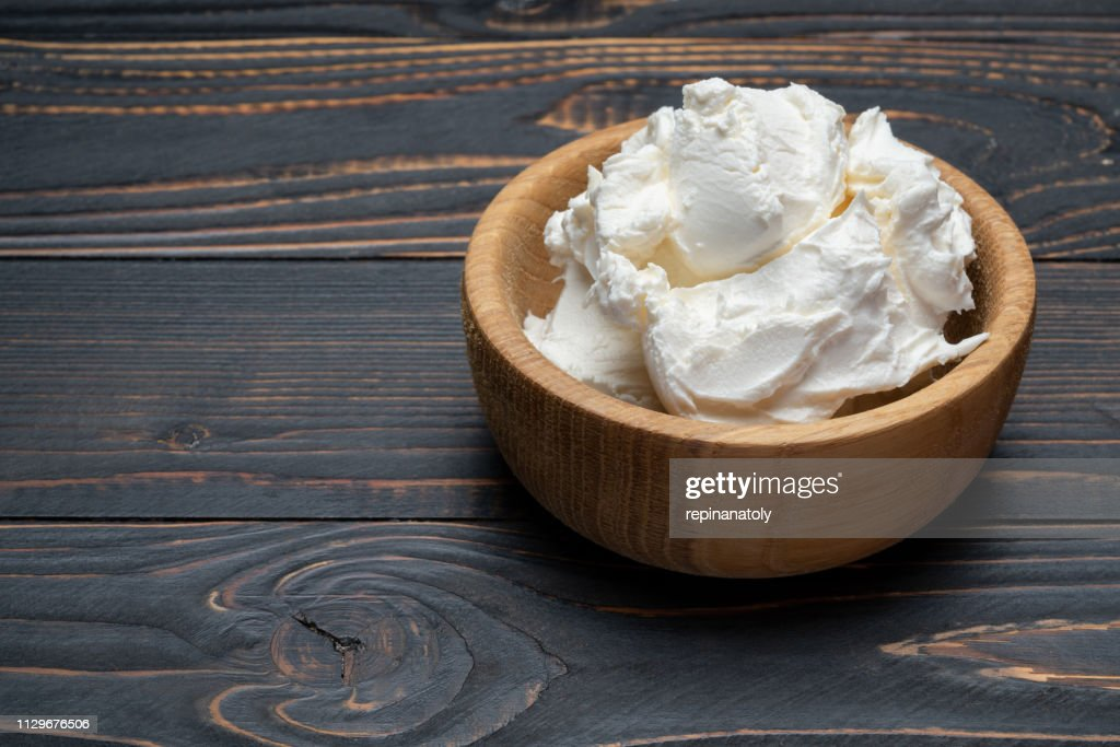 Traditional Mascarpone cheese in wooden bowl on table : Stock Photo