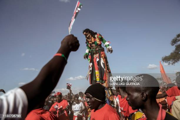 TOPSHOT A traditional masked man on stilts entertains Malawi Congress Party leader and Presidential candidate supporters waiting for his arrival at...