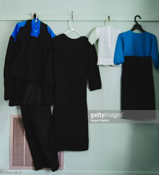traditional mens and womens amish clothing, hanging on a green wall - blue dress stock pictures, royalty-free photos & images
