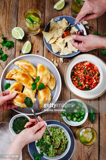 traditional mexican food - meat empanadas with cilantro chimichurri sauce,  guacamole, salsa, tortilla chips and mojito. couple eating mexican food - savoury food stock photos and pictures