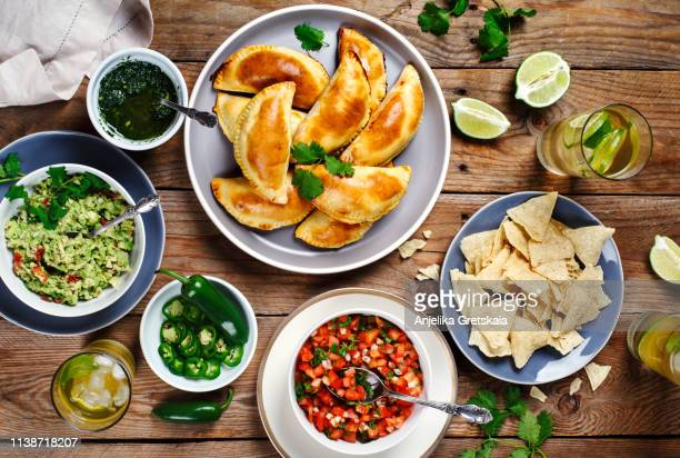 traditional mexican food - meat empanadas with cilantro chimichurri sauce,  guacamole, salsa, tortilla chips and mojito - empanada stock pictures, royalty-free photos & images