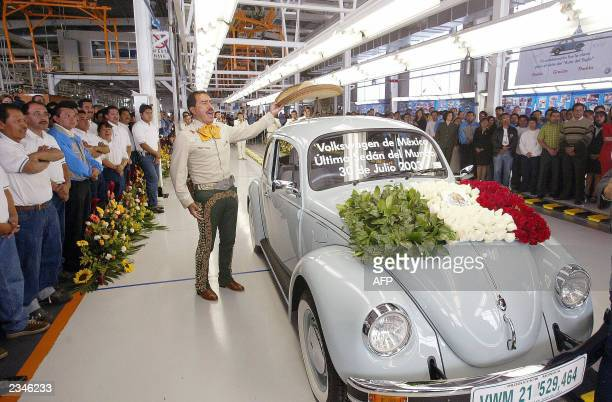 A traditional Mexican Mariachi musician places his sombrero on the roof of the very last VW Beetle as it rolls off the production line at VW's Puebla...
