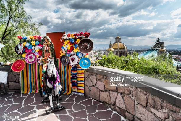 traditional mexican tourist knick knacks for sale near the guadalupe basilica church and mexico city skyline - festival de la virgen de guadalupe fotografías e imágenes de stock