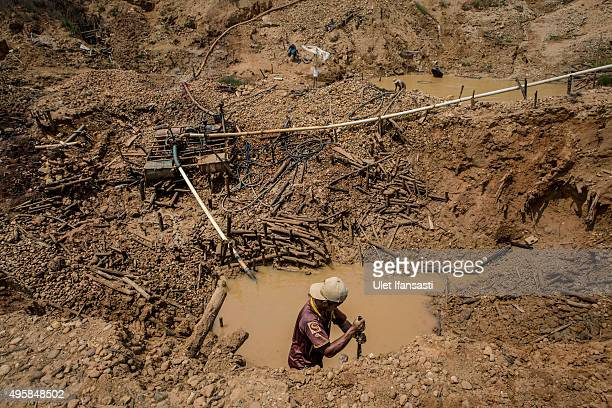 A traditional miner digs in mud as he searches for diamonds in Cempaka village at Martapura also known as the City of Diamond on November 4 2015 in...