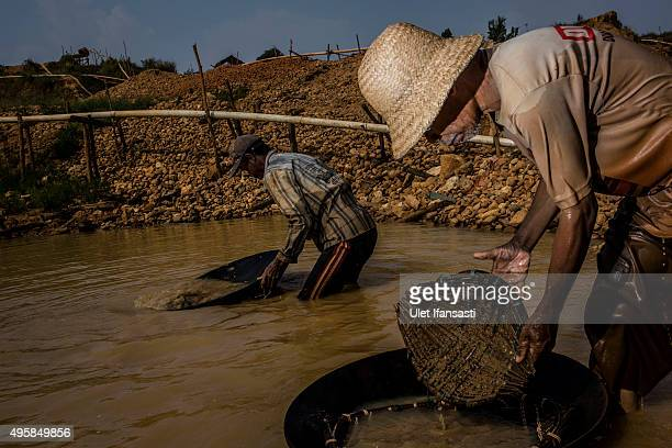 A traditional miner Sya'rani right washes mud in conical bowls known as 'Linggang' as they search for diamond in Cempaka village at Martapura also...