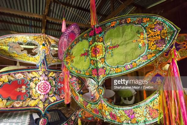 traditional moon kite or locally known as wau bulan on display at traditional workshop in malaysia. - shaifulzamri stock pictures, royalty-free photos & images
