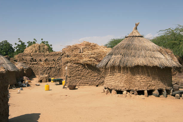 A traditional mud house with thatched roof in a village Dantchadi, Sahel Region of Burkina Faso.