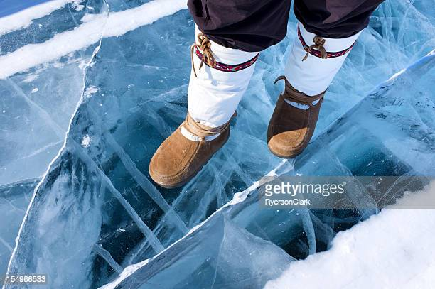 traditional mukluks or boots on ice. - inuit stock pictures, royalty-free photos & images