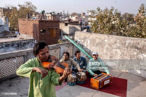 Traditional musicians play on a roof top in Chandni Mahal, Old Delhi, India. Once patronised by the Mughal rulers many now scrape a living playing...