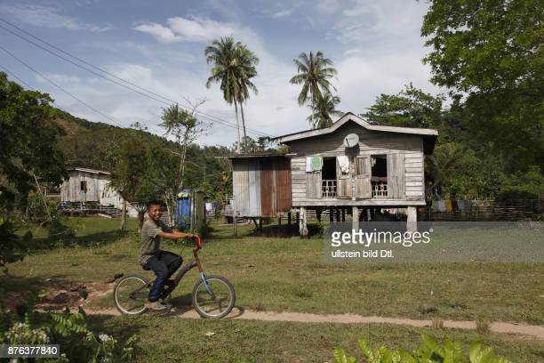 Traditional native Iban and Dayak boy on a bycicle by a longhouse in Borneo Malaysia