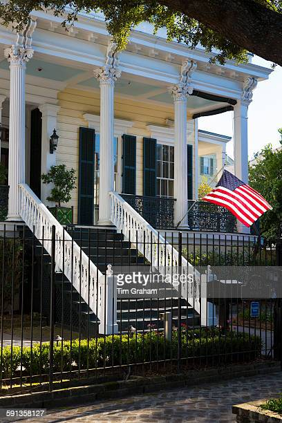 Traditional neoclassical clapboard grand house with columns stars and stripes flag in the Garden District New Orleans USA