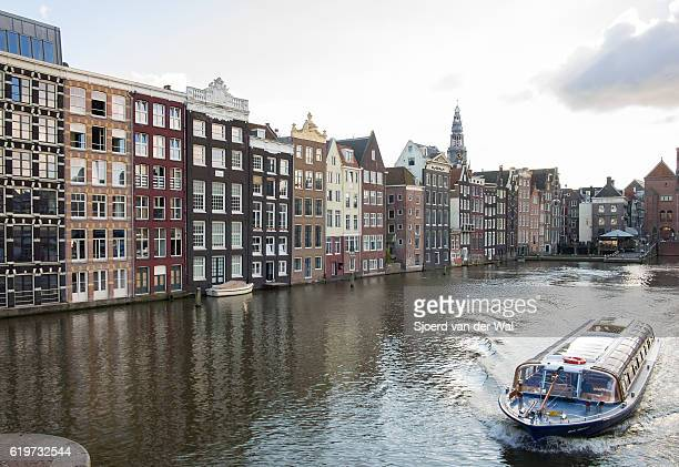 "traditional old buildings at a canal in amsterdam, the netherlands - ""sjoerd van der wal"" stockfoto's en -beelden"