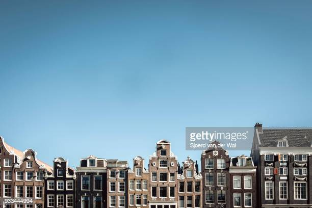 "traditional old buildings facades at to the canals in amsterdam, the capitol of the netherlands. the ancient merchant's houses are located at the ring of canals in the city centre. - ""sjoerd van der wal"" stock-fotos und bilder"