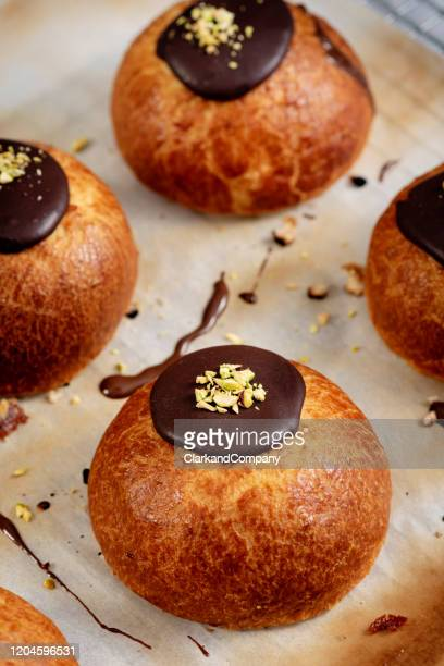 traditional old fashioned fastelavnboller or danish cream cakes topped with pistachios - danish culture stock pictures, royalty-free photos & images