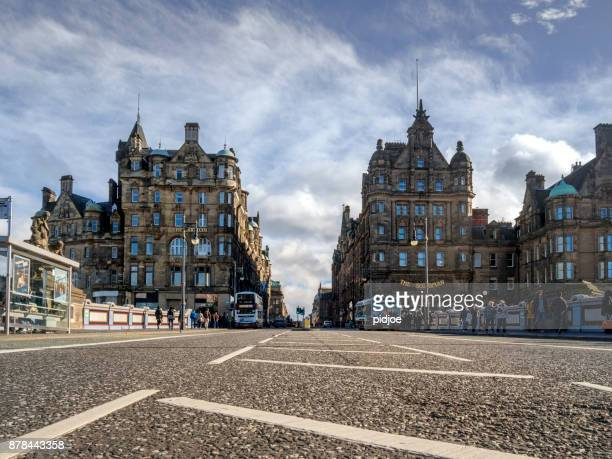 traditional old gothic buildings on north bridge in downtown edinburgh scotland england uk. this image is gps tagged - balmoral hotel stock photos and pictures