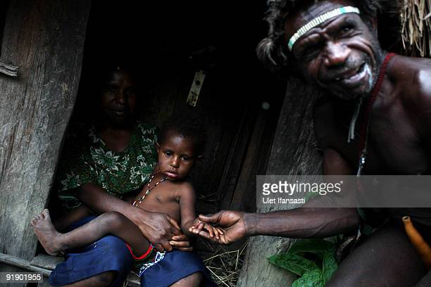 Traditional peoples of the Dani tribe from Lembah Baliem are sitting in front of their house on October 10 2009 in Wamena West Papua Indonesia The...