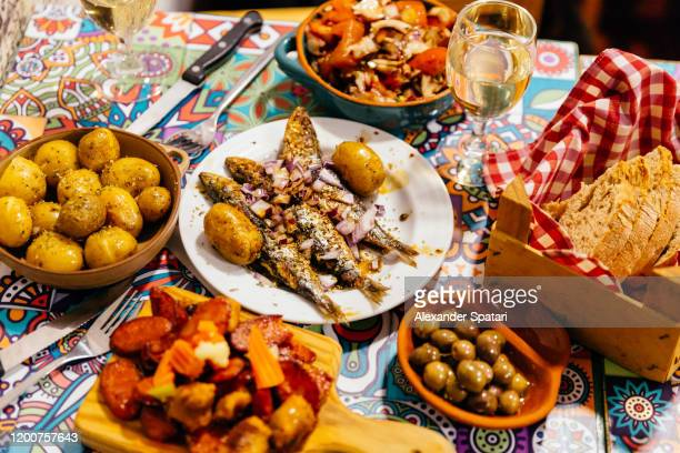 traditional portuguese dinner with grilled sardines, potatoes, olives, octopus salad and fresh bread, lisbon, portugal - cultura portoghese foto e immagini stock