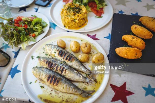 traditional portuguese dishes of grilled sardines, bolinhos de bacalhau and bacalhau a bras, portugal - local landmark stock pictures, royalty-free photos & images
