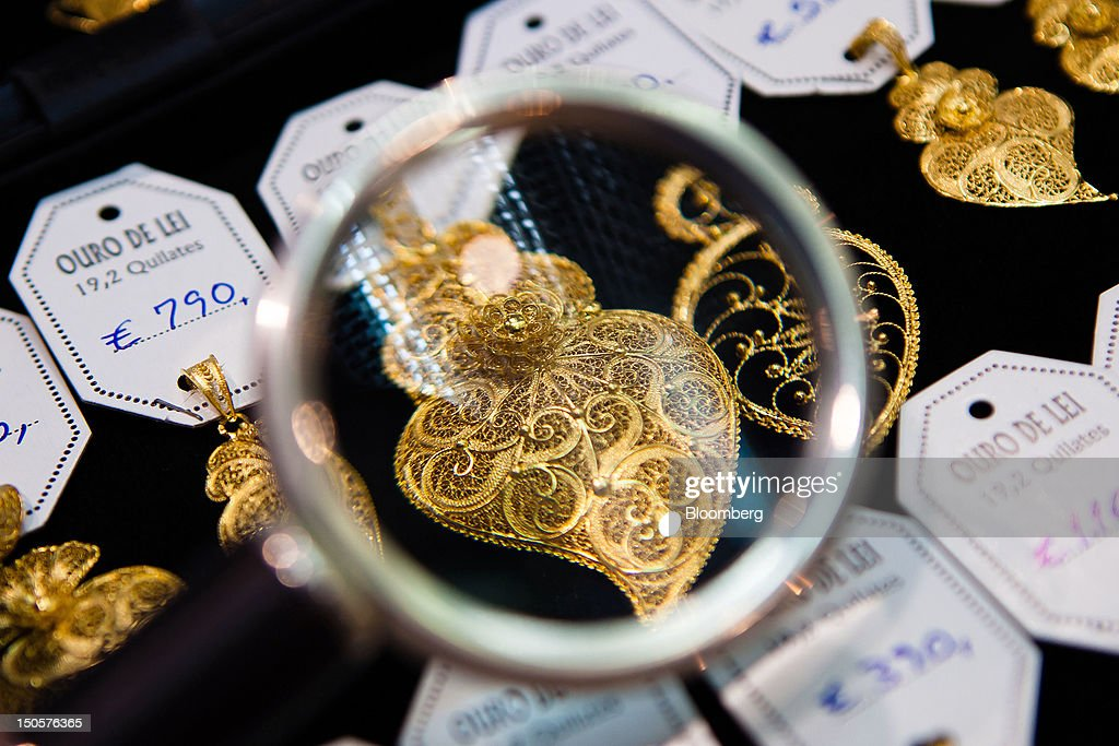 Traditional Portuguese gold jewelry is seen through a magnifier as it sits on display beside euro price tags in the window of a jewelry store in Lisbon, Portugal, on Wednesday, Aug. 22, 2012. In Portugal, the historical home of some of Europe's biggest gold reserves, the number of jewelry stores, which include cash-for-gold shops, increased 29 percent in 2011 from a year earlier, a study commissioned by parliament found. Photographer: Mario Proenca/Bloomberg via Getty Images